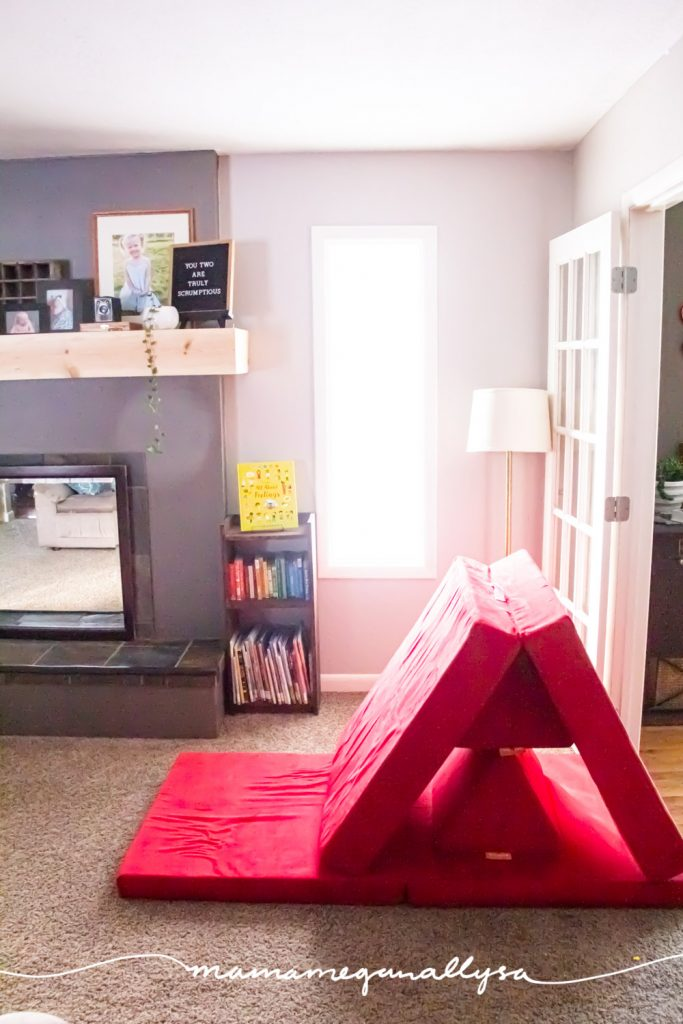 our red nugget play couch set up like a slide in front of a window in our living room playroom