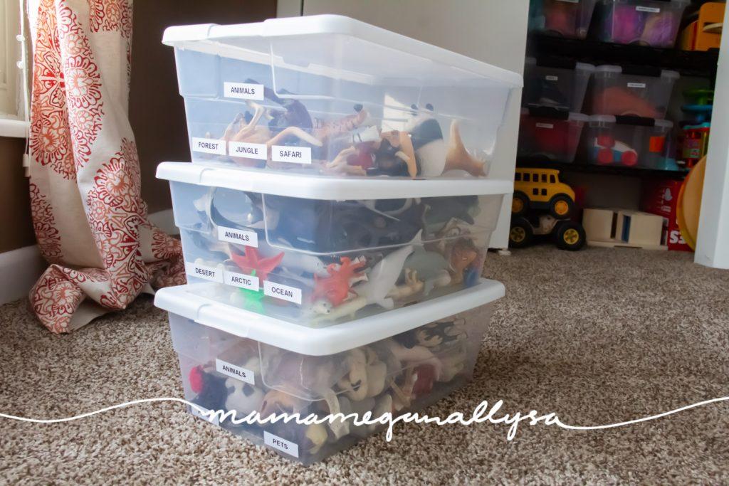 three shoebox-sized plastic bins holding our plastic animal bin
