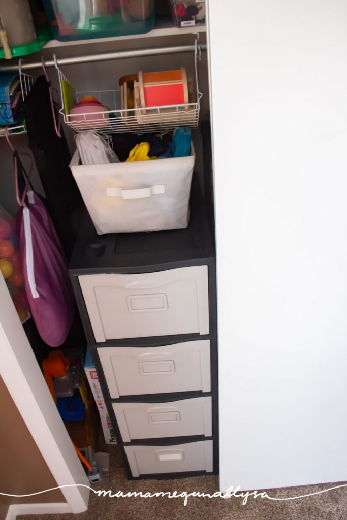a toy storage closet with a file cabinet and wire hanging shelves