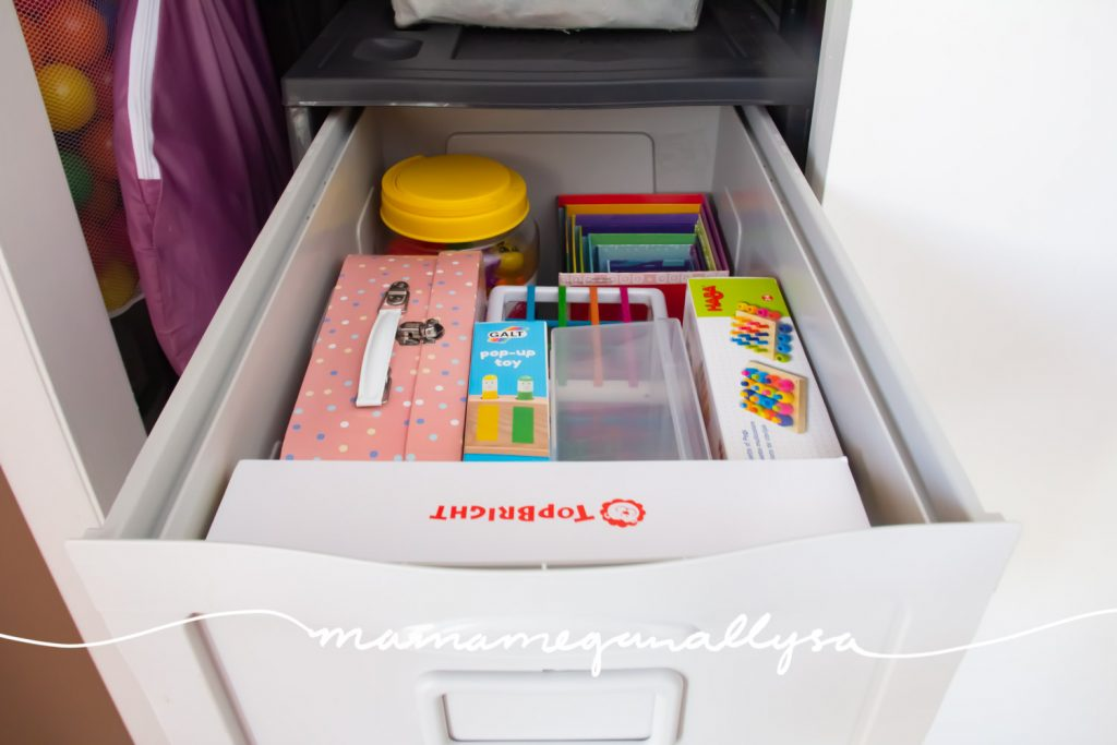 a filing cabinet drawer with some toys in boxes
