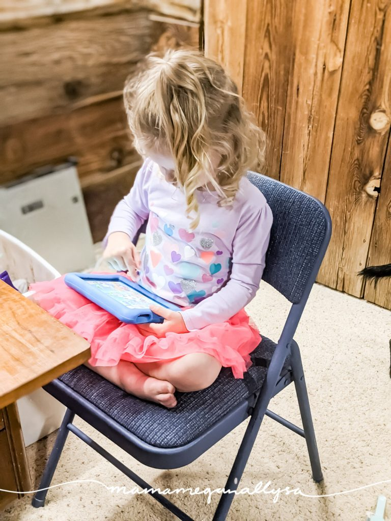 a little girl playing on her tablet