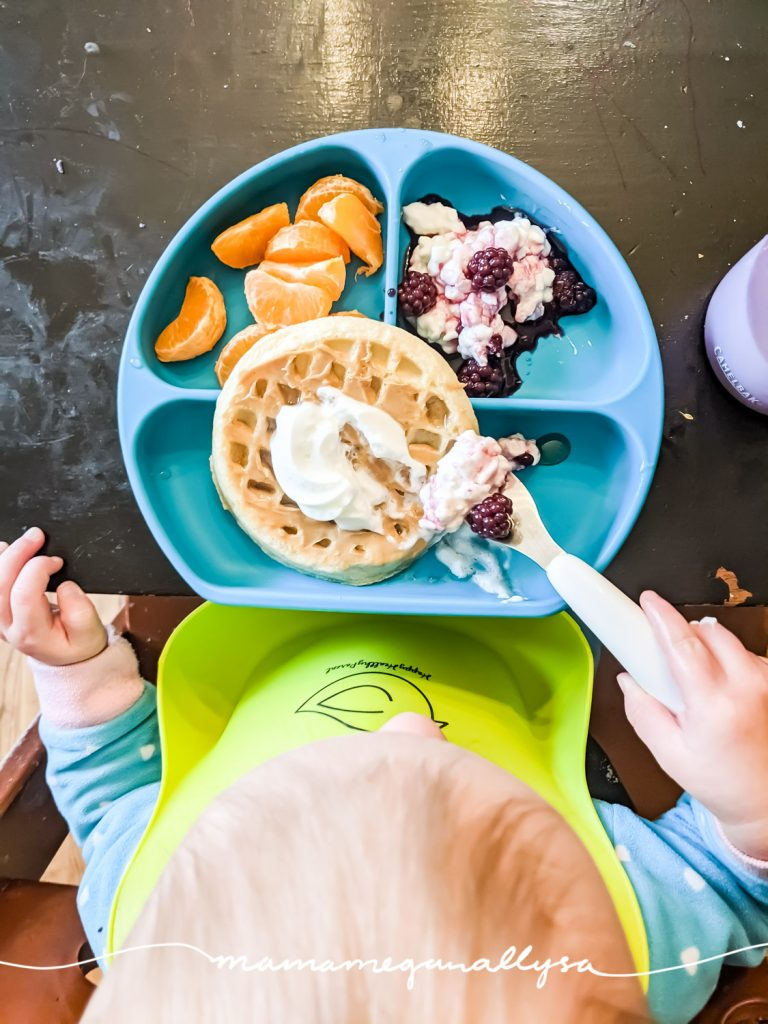 a top-down shot of a toddler eating her breakfast