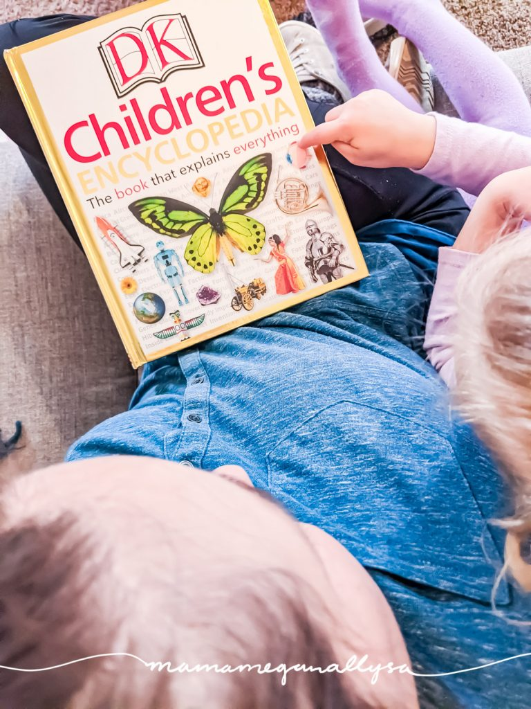 a children's encyclopedia in a moms lap with a preschooler pointing at the cover