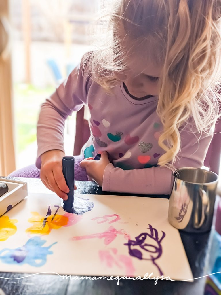 a little girl using a purple paint stick to color a picture
