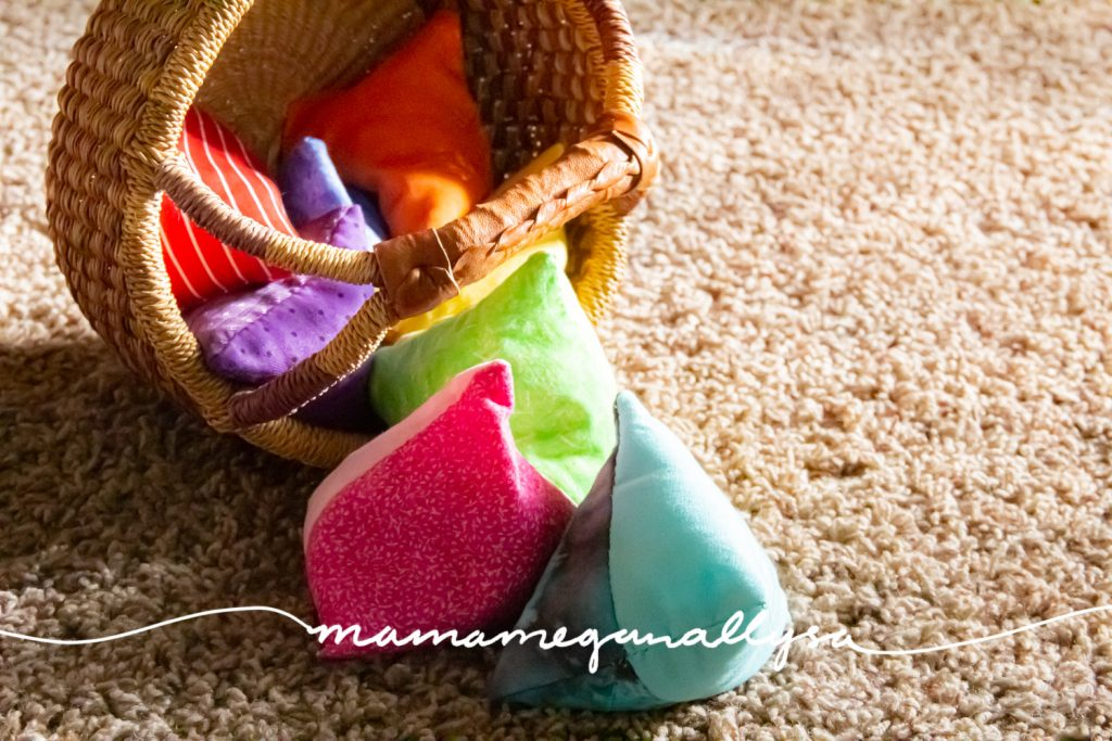 a close up of a basket with a rainbow of homemade bean bags