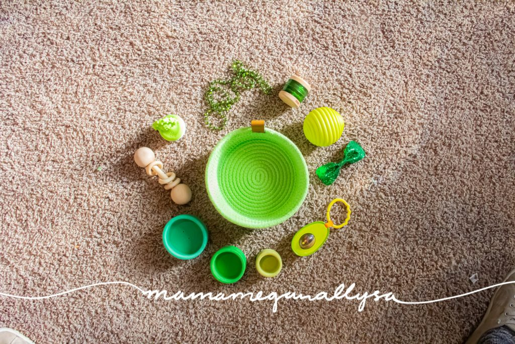 a lime green rope basket on the floor surrounded by green baby toys