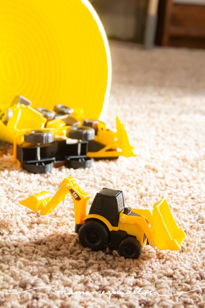 a close up of our mini construction trucks in front of a yellow basket