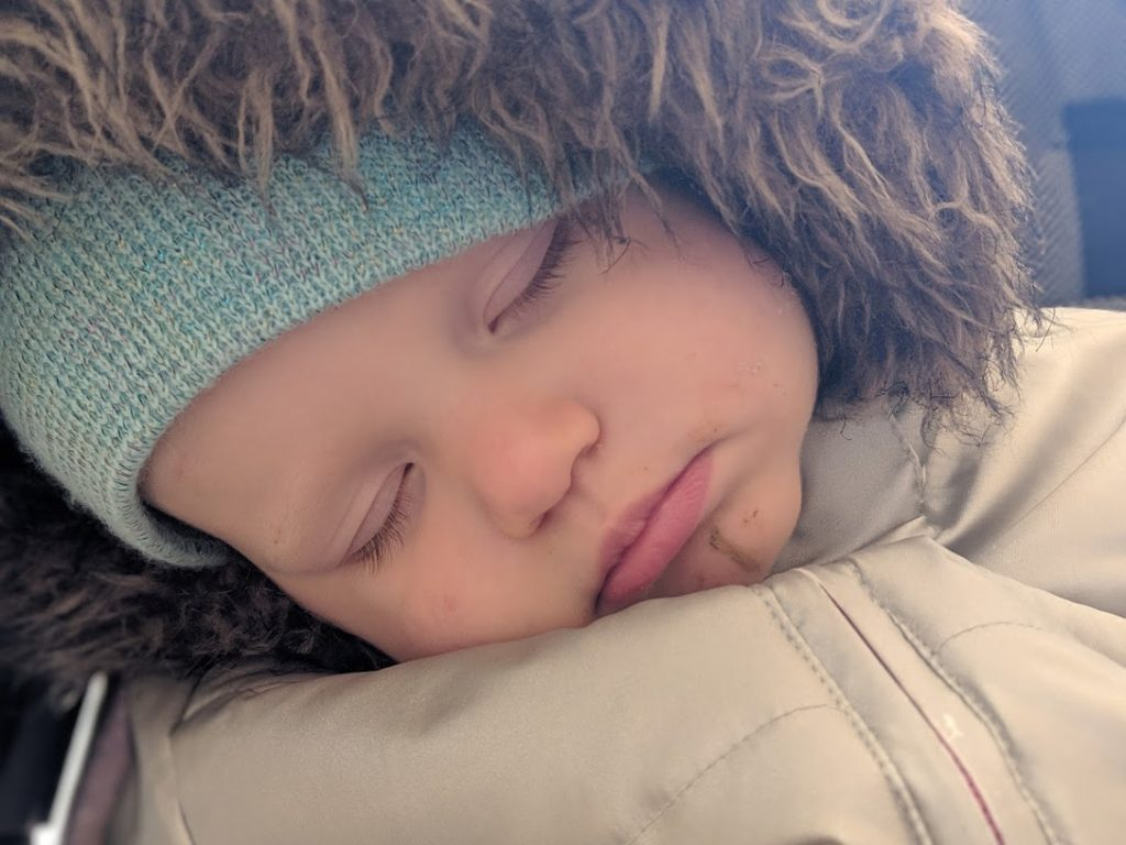 a toddler asleep in a stroller with a blue hat and a fur lined hood
