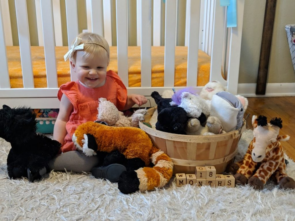 a girl toddler surrounded my all her stuffed animals in her room.