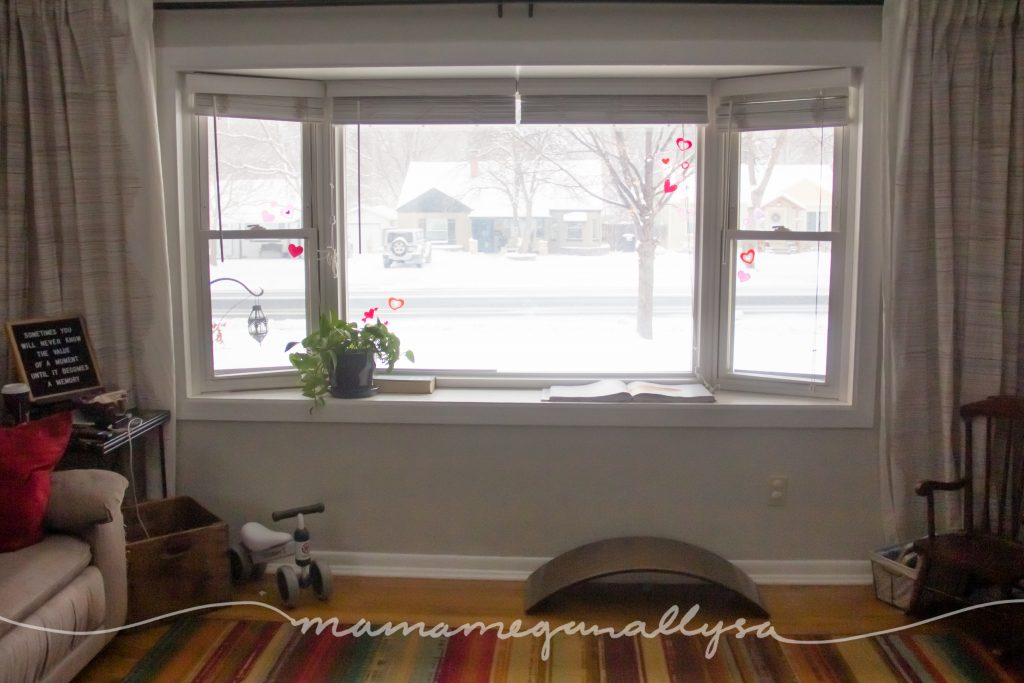 a large bay window with a wobble board and toddler ride on toy on the floor
