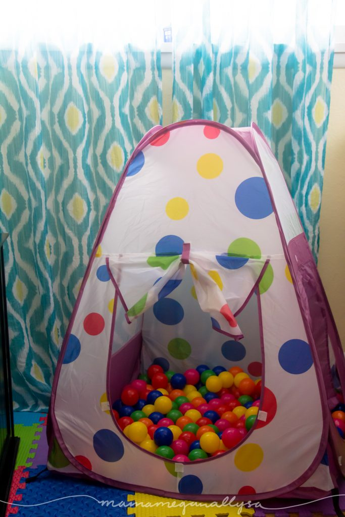 a tent and ball pit in set up as a toddler play space in an office