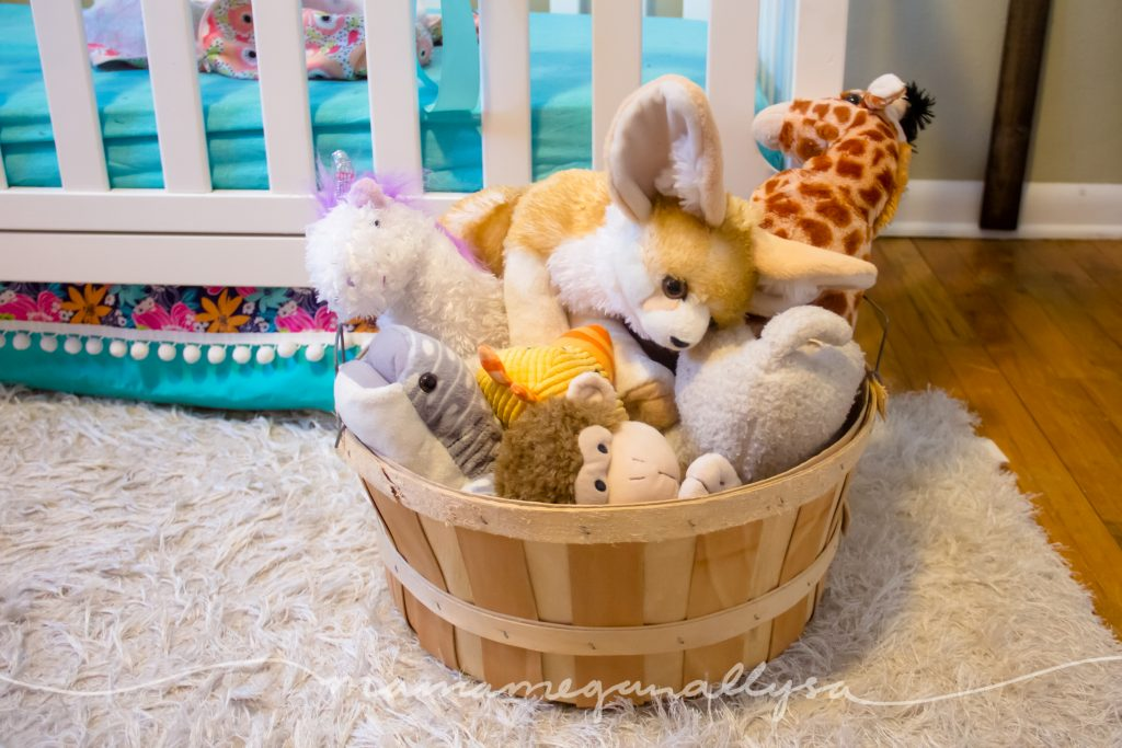 a basket overflowing with stuffed animals in a toddlers room