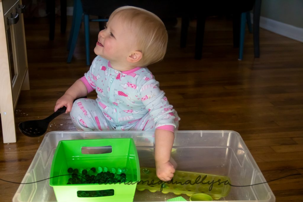 a toddler smiling while playing with the green water bead sensory bin