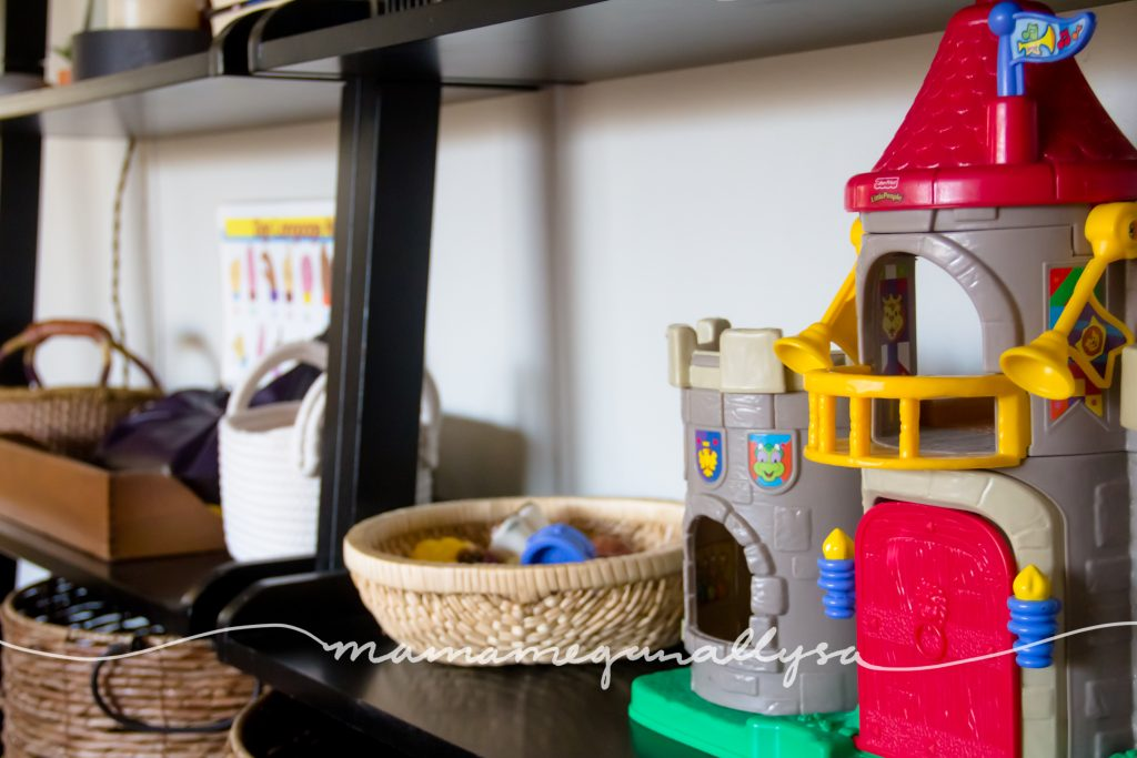 An overview of her play shelf with her Little peoples castle and other baskets of toys