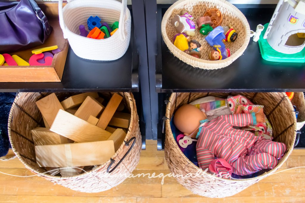Her big baskets on the bottom of the play shelf, full of wooden blocks and baby dolls