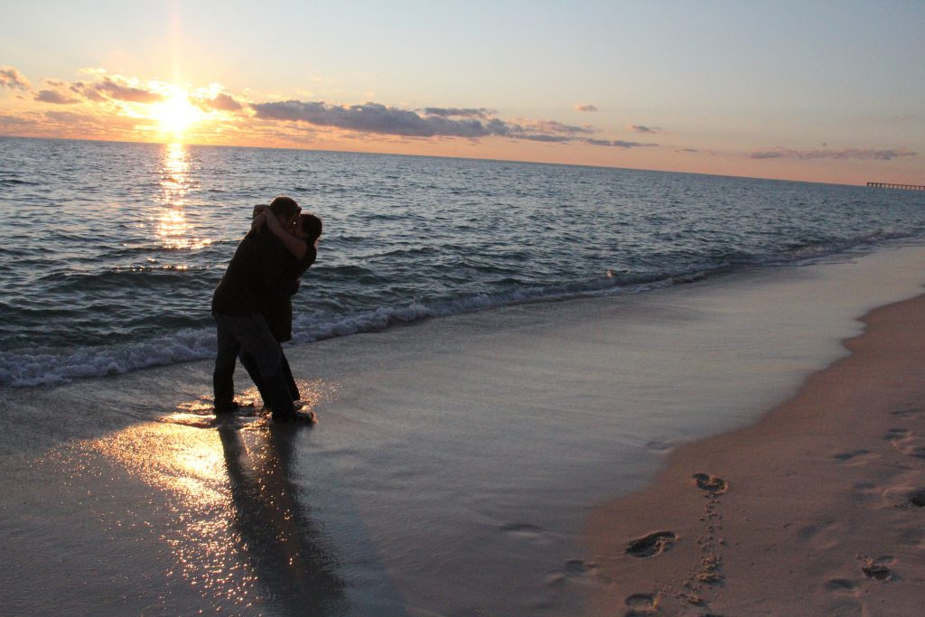 a young couple kissing on the beach at sunset with the waves at their feet