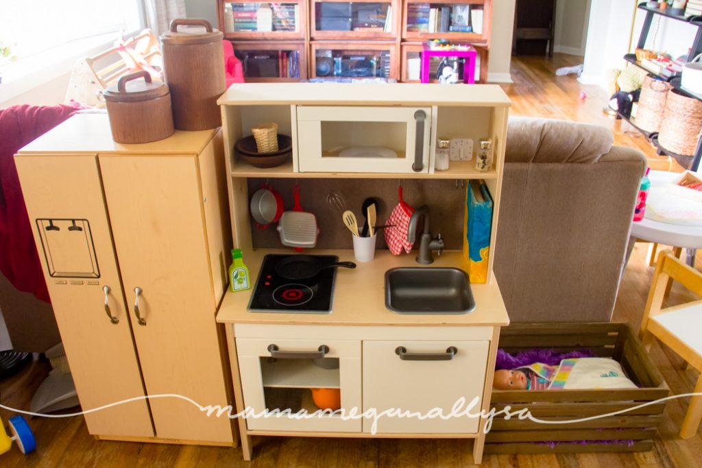 a dramatic play home space with an ikea play kitchen, play fridge and wooden crate for a baby crib