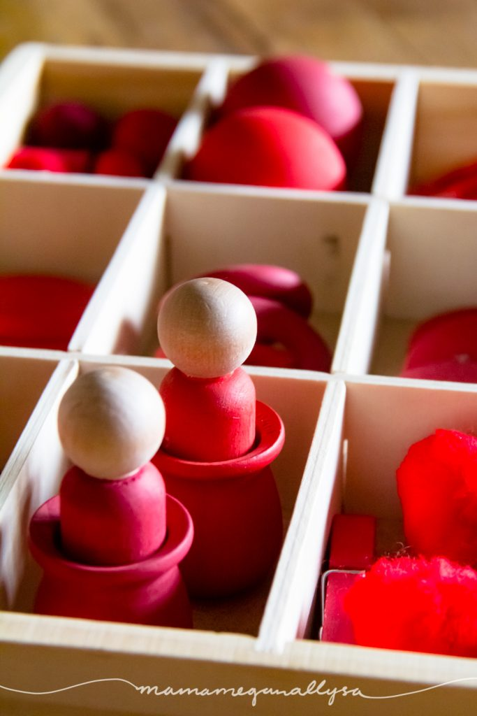 red wooden loose parts toys in a divided tray