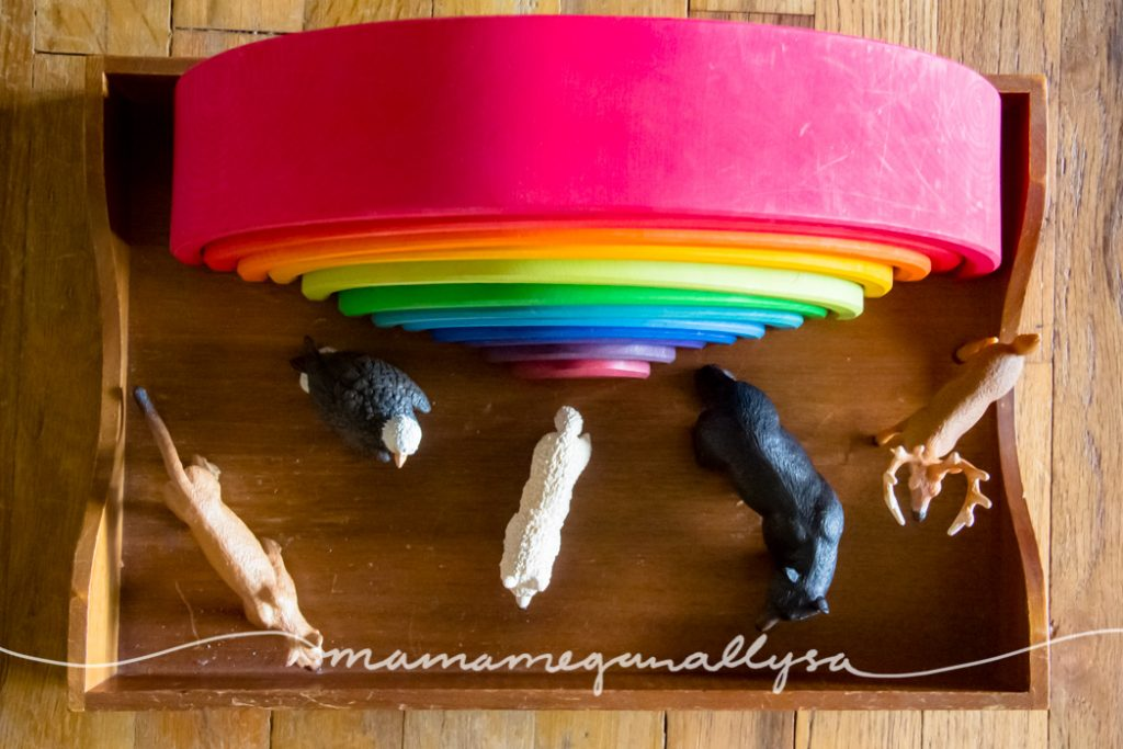 a Grimms rainbow stacker toy with forest animal figures in front of it on a wooden tray
