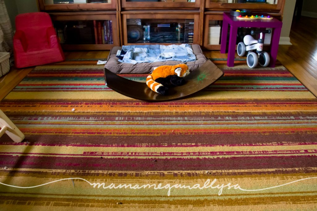 a living room play space with a wobble board small play table and baby bike