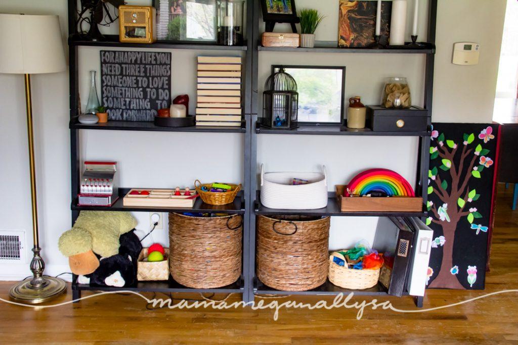 Black living room bookshelves with toys on the bottom two shelves