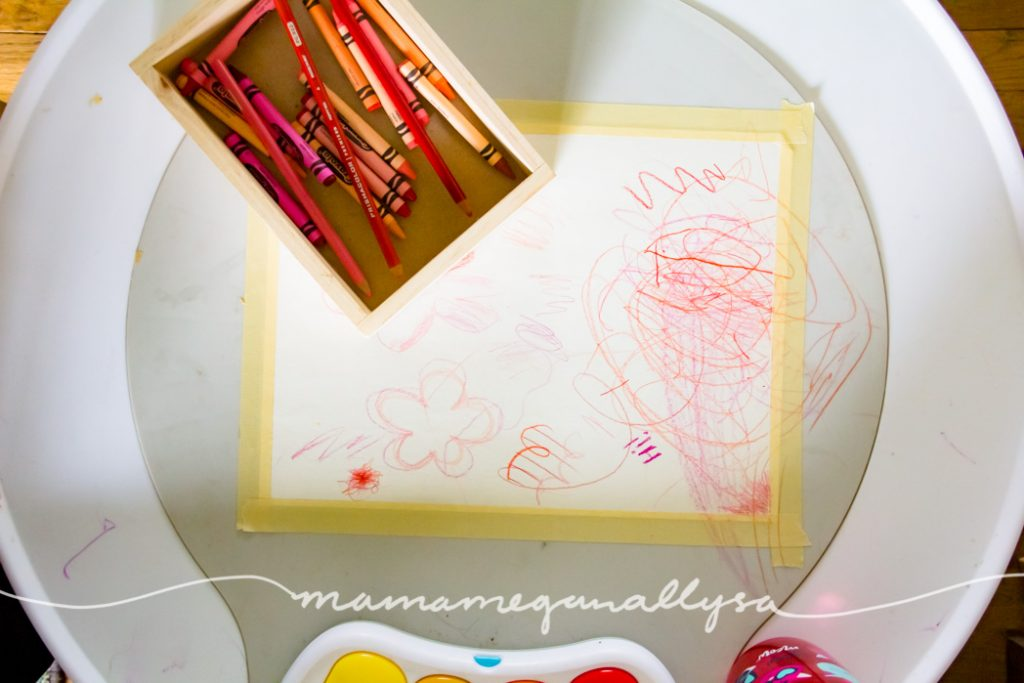 a white play table with a peice of paper taped down with toddler scribbles all over it