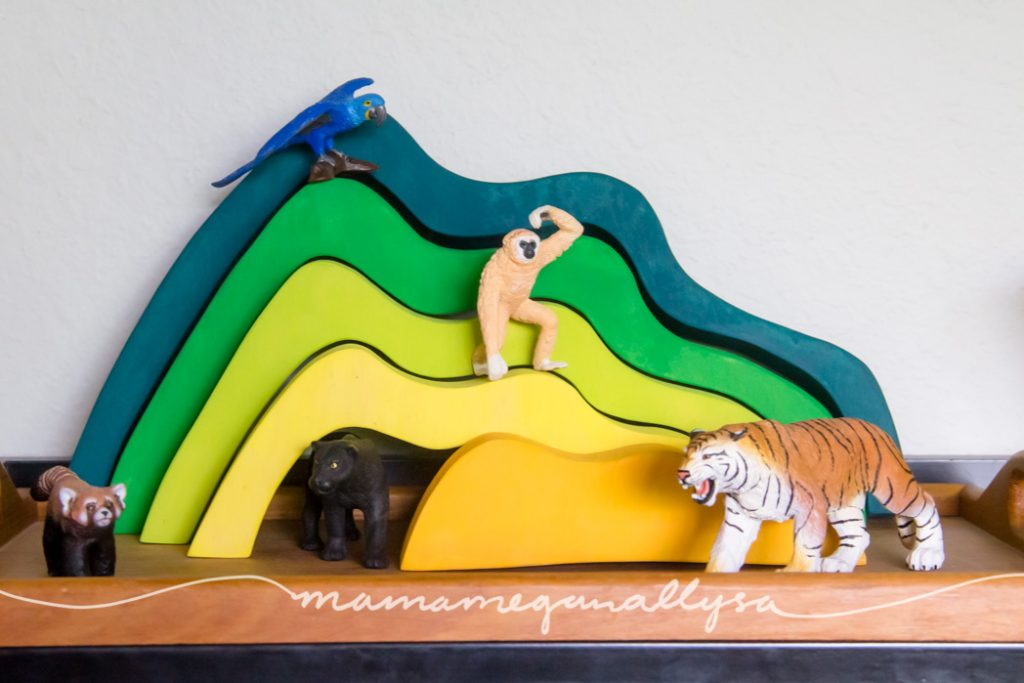 an overview of the homemade hill stacker with her jungle animals staged around it