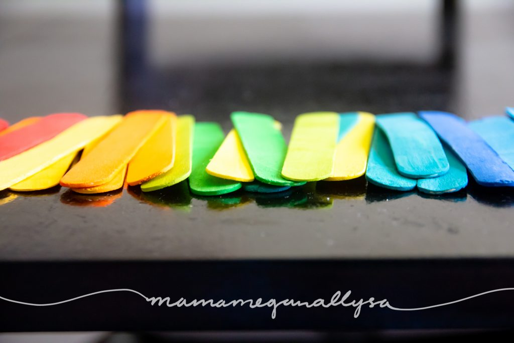 close up of our rainbow hand-painted popsicle sticks for loose parts play