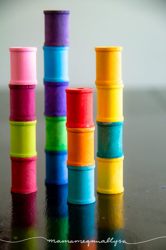 rainbow hand-painted wooden spools stacked up