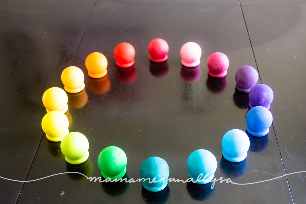 rainbow hand-painted wooden balls stacked on our wooden rings