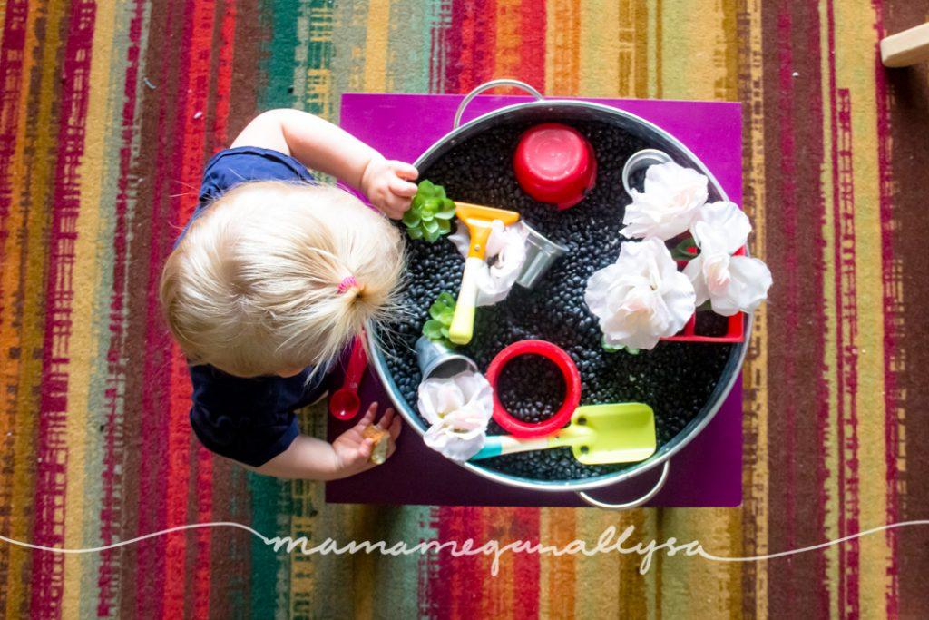 Top down view of a toddler playing in a black bean garden sensory bin