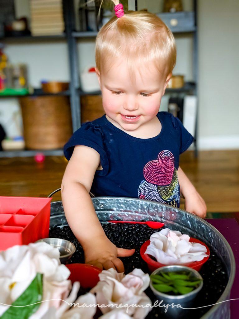 A toddler in a blue shirt playing in a black bean garden sensory bin