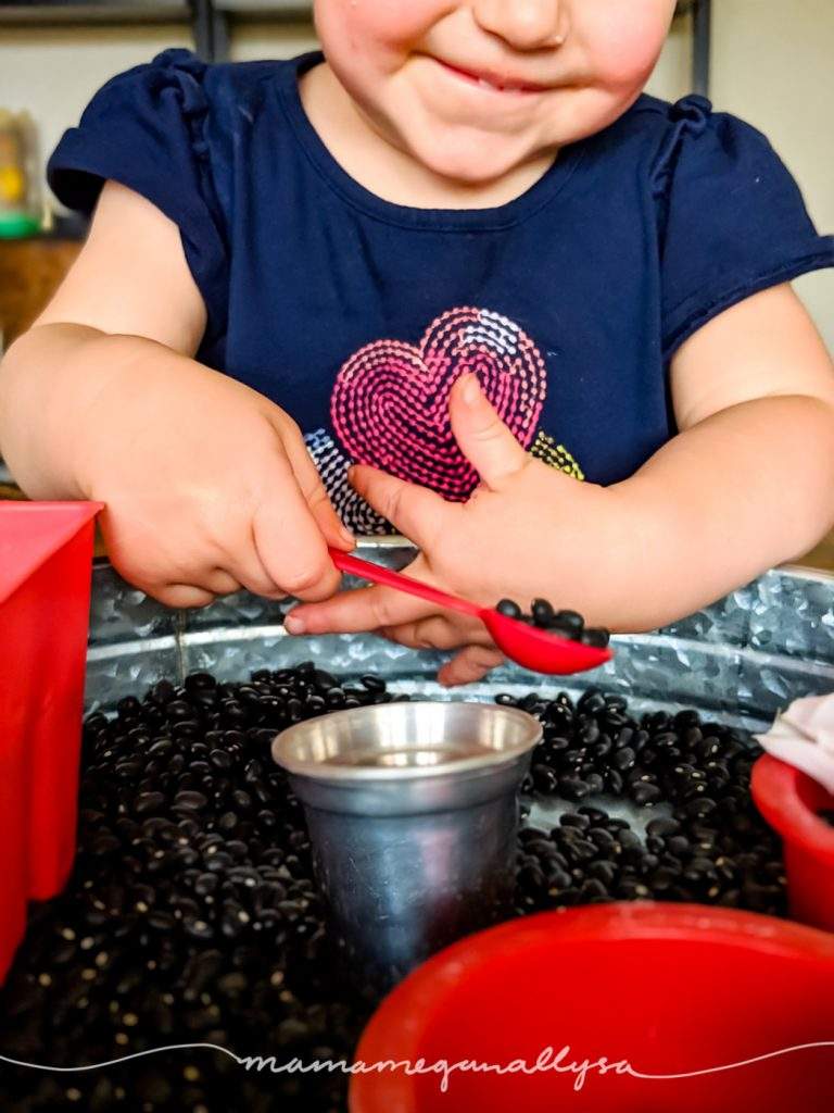 a toddler smiling holding a measuring spoon filled with black beans