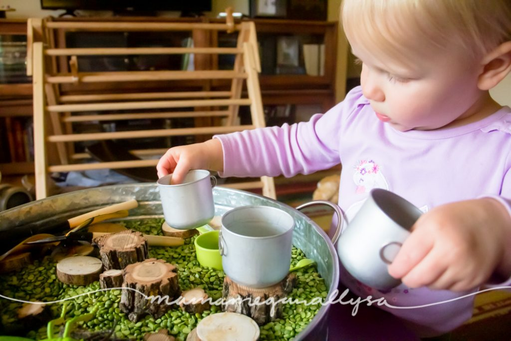 a toddler playing with mini nesting metal pots