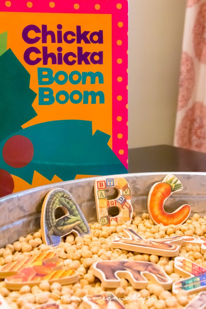 a close up of the puzzle letters in the tray of chick peas with Chicka Chikca Boom Boom book propped up behind the tray