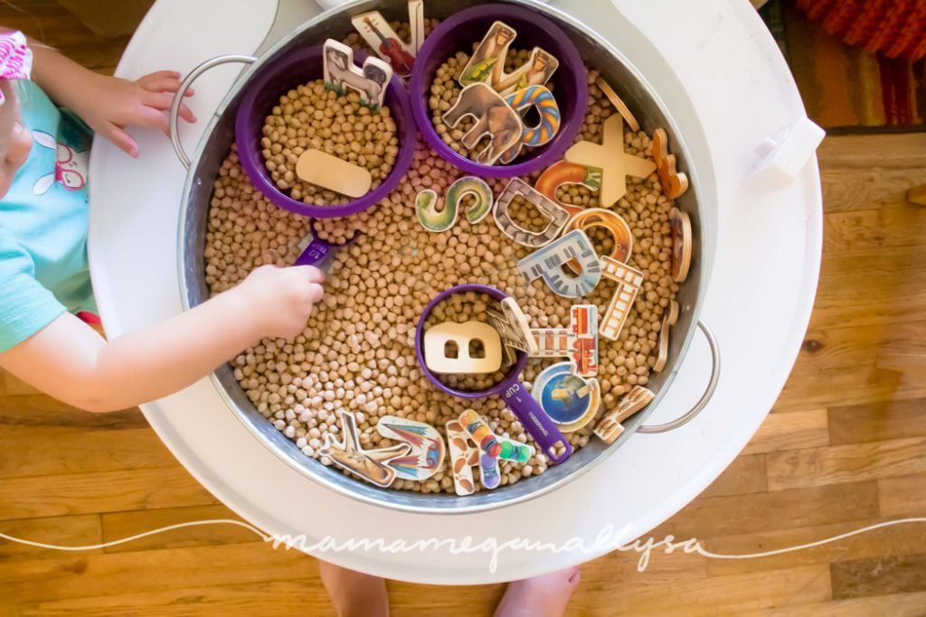 a toddler scooping in the ABC's and Chick Peas sensory bin