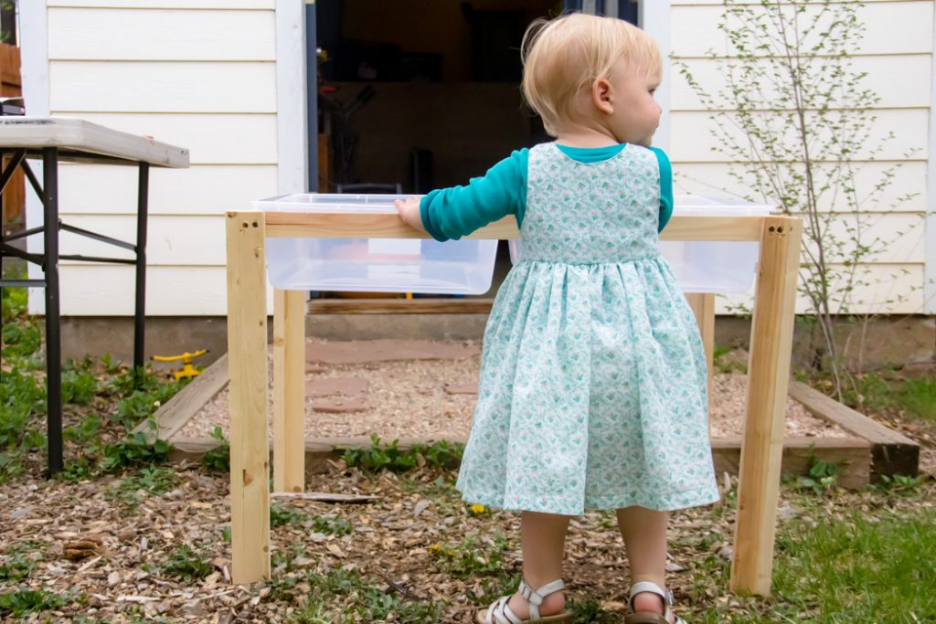 toddler standing at the side of the table