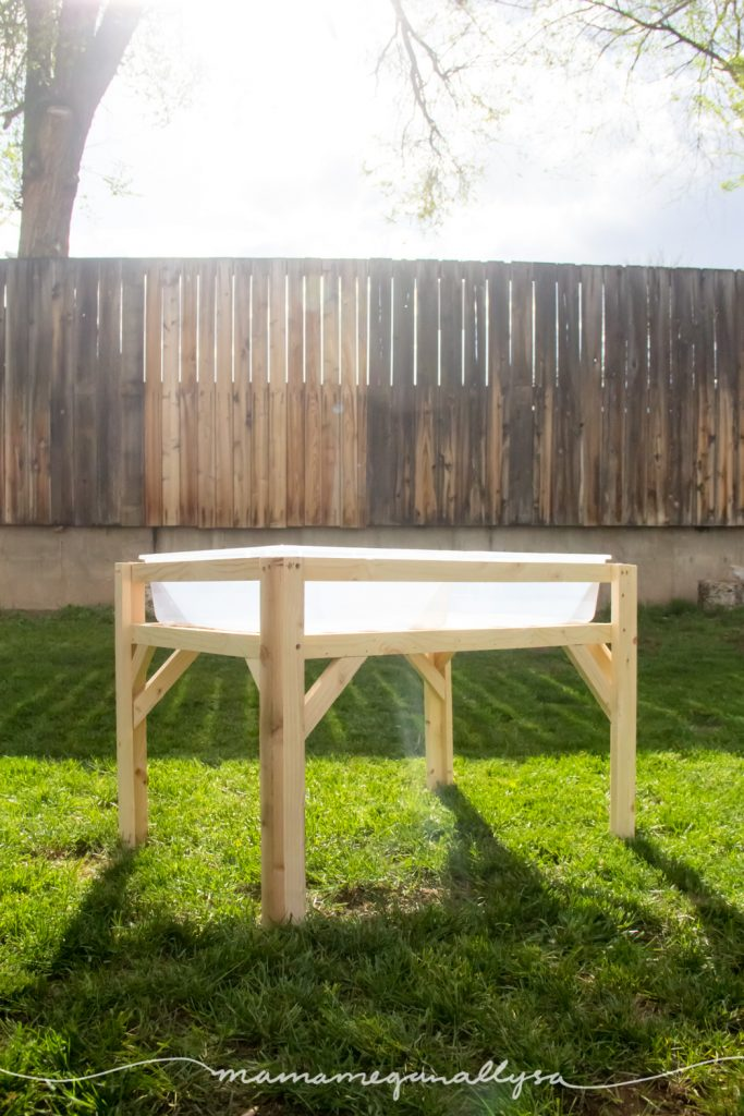 fully constructed DIY sensory bin table sitting the yard with backlit sunlight