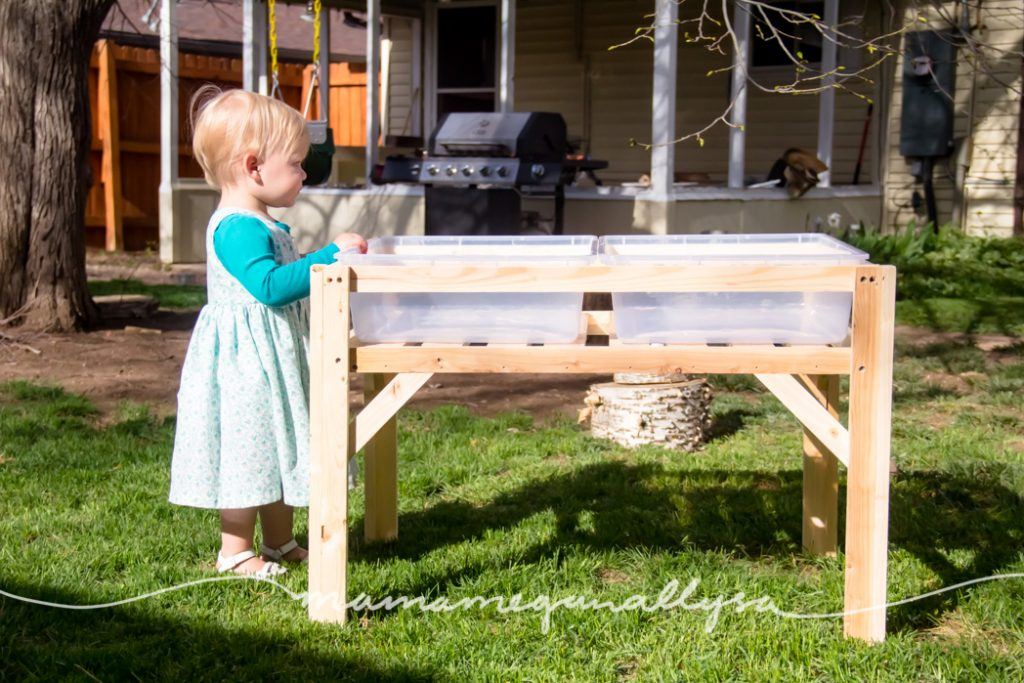 toddler standing next to DIY sensory bin table showing how high it hits on her