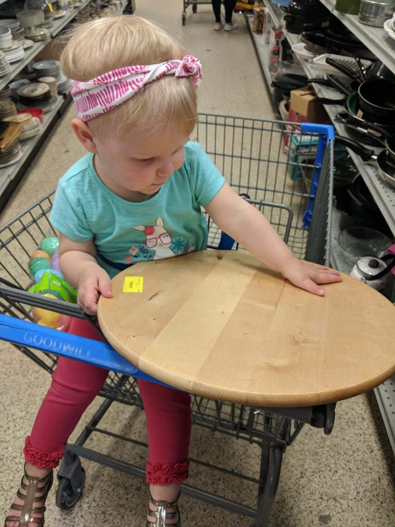 a toddler holding a wooden lazy susan in Goodwill after months of searching