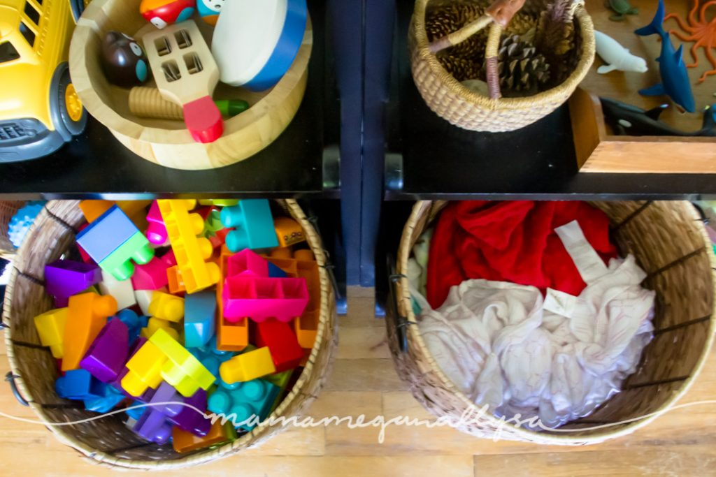 large wicker baskets filled with Megablocks and babydolls on the bottom of the play shelf