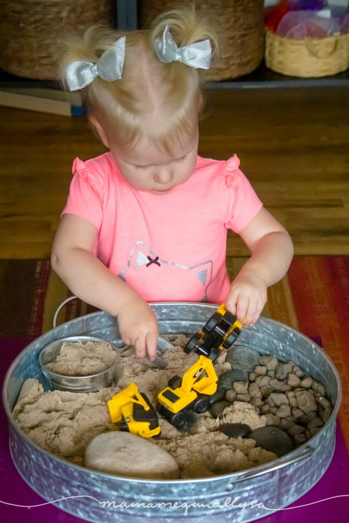 a toddler loading up a construction truck with sand