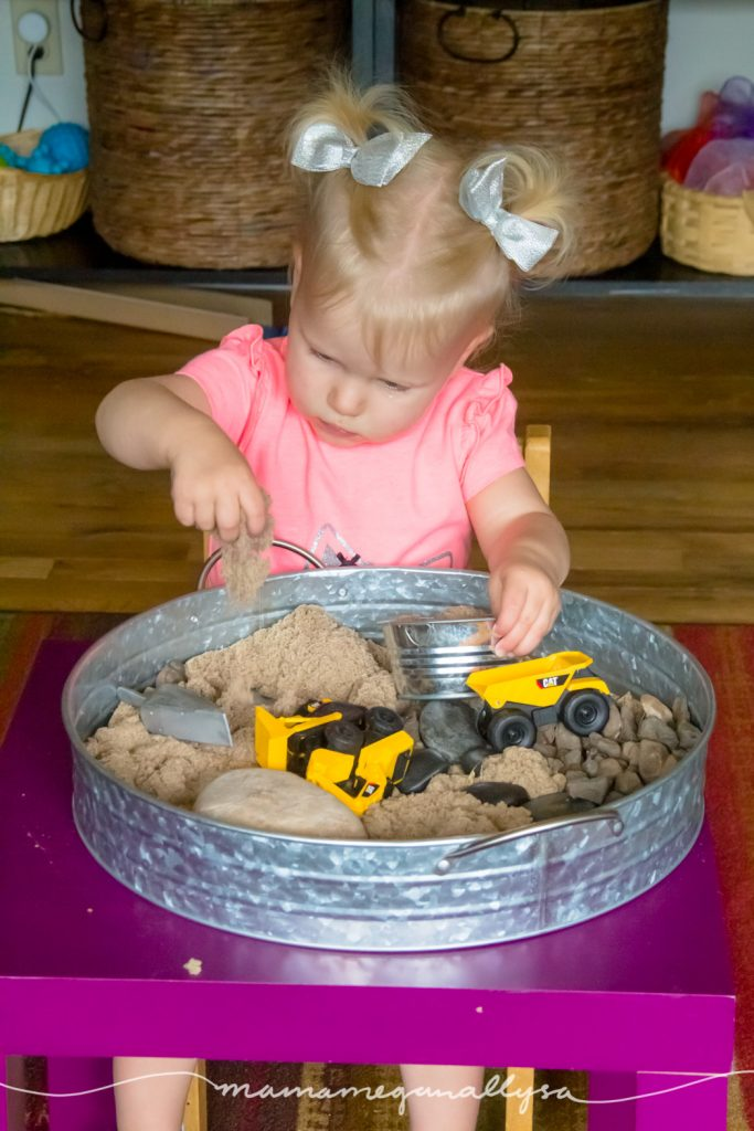 a toddler playin in kinetic sand sitting a table with a sensory bin in front of her