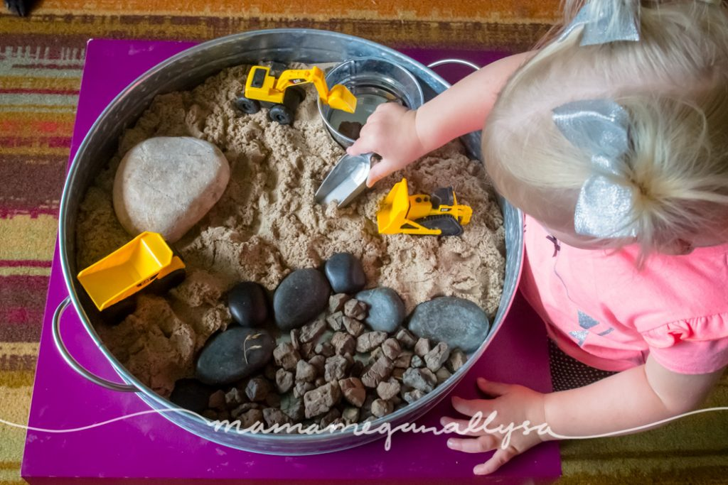 a toddler using a scoop in a tray of kinetic sand and stones