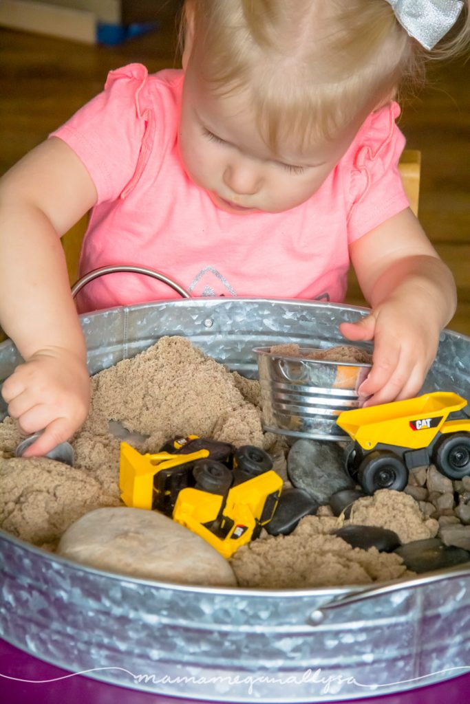 a toddler digging in the kinetic sand on out construction trucks sensory bin