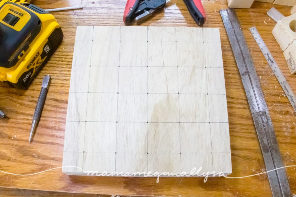 the grid drawn out on the block of wood for the peg people board