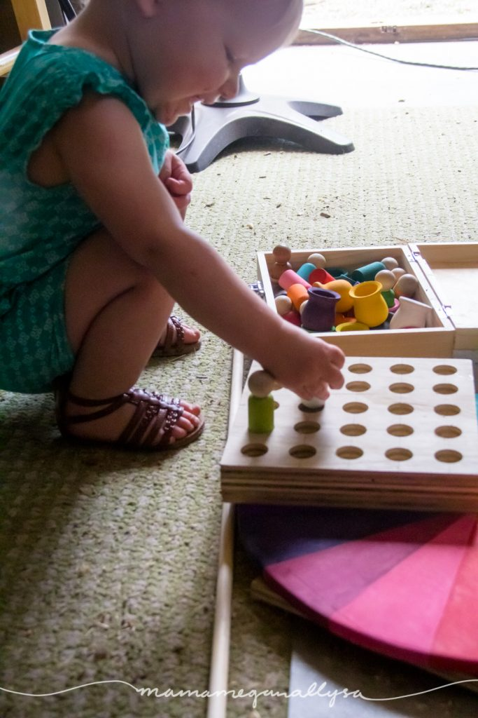 a toddler happily inserting wooden peg people into the peg board