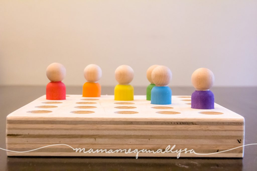 wooden peg people inserted into the peg people board loose parts tool