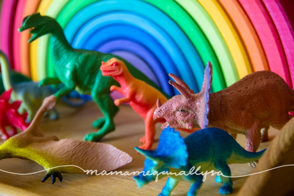 a rainbow of dinosaurs in front of a Grimms rainbow