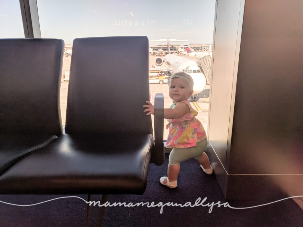 a young toddler watching the airplanes out the window at the airport
